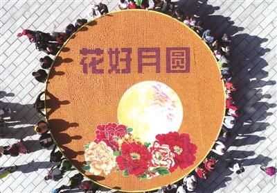 """景区工作人员用9999枚月饼绘制成""""花好月圆""""的图案为中秋送上祝福."""